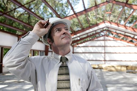 rafters: A construction engineer surveying his steel frame building with pride. Stock Photo