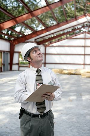 A vertical view of a construction inspector looking at a steel frame building.  Room for text. photo