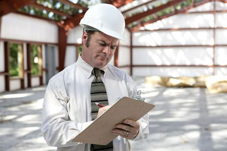 An unhappy looking construction inspector marking his checklist on a construction site.
