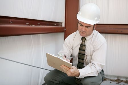 A construction inspector on a jobsite making notations on his clipboard.   photo