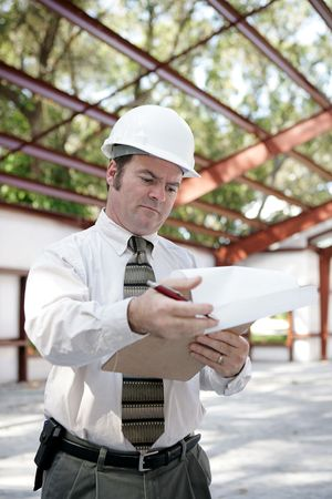 business skeptical: A building inspector on site reviewing his notes.  Vertical view.