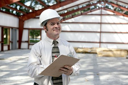 A construction inspector satisfied with his inspection of a steel framed building. photo