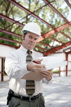 A skeptical looking construction inspector going over his notes and pointing out problems.