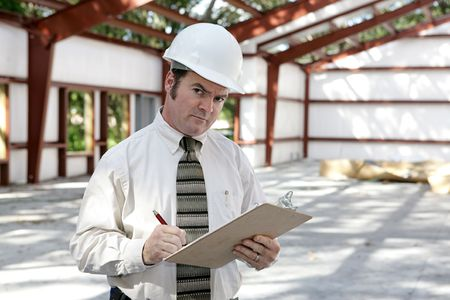 A construction inspector in a steel frame building making notes and looking suspicious.