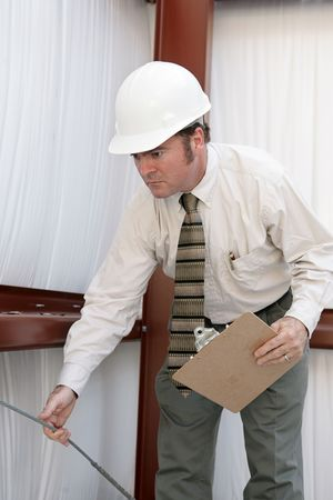 A building inspector testing the tension on a support wire in a steel frame bulding. photo