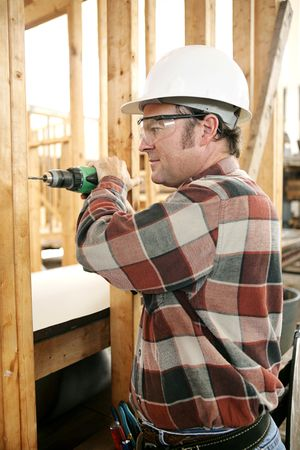 A carpenter on a construction site drilling safely according to safty codes and regulations.   photo