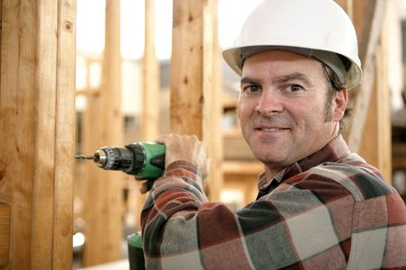 A carpenter using a battery powered drill on a construction site. photo