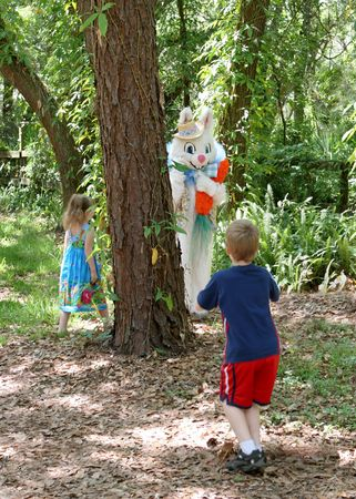 buck teeth: The Easter Bunny playing hide and seek with two young children.