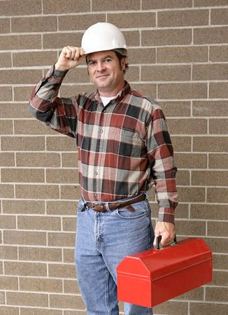tipping: A handsome construction worker carrying his toolbox and tipping his hard hat.