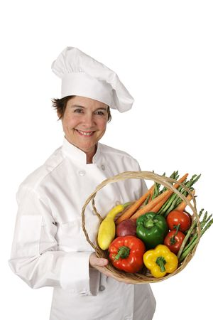 A pretty chef holding a basket of fresh vegetables.  Isolated on white. Stock Photo - 806084