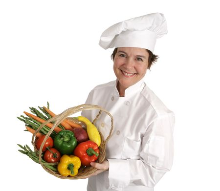 An attractive female chef holding a basket of delicious fresh vegetables.  Isolated on white. photo