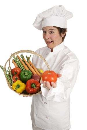 A chef holding a basket of vegetables and offering a tomato.  Isolated on white. Stock Photo - 806087