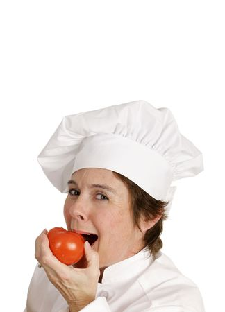 A pretty female chef biting into a juicy red tomato.  Isolated with room for text. Stock Photo - 806089