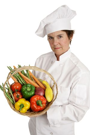A female chef holding a basket of vegetables with a serious expression.  She takes nutrition seriously.  Isolated on white. Stock Photo - 806090