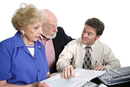 suggested: A senior couple going over their taxes with a shady accountant.  He has just suggested something sneaky.  Isolated on white.