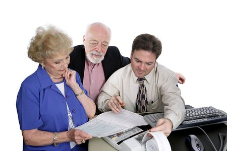 A successful senior couple going over figures with their accountant.   photo