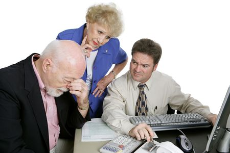 A senior couple and their accountant worried over their financial future. photo