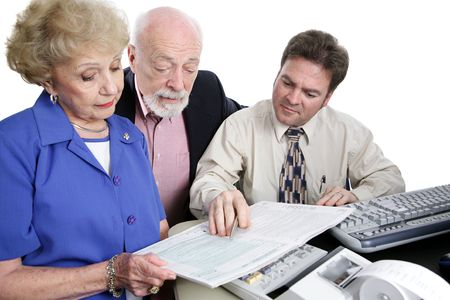 A senior couple going over the tax booklet with their accountant.  Isolated on white. photo
