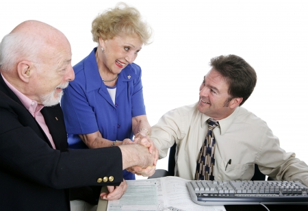 A senior couple shaking hands with their accountant.  Isolated on white.   版權商用圖片