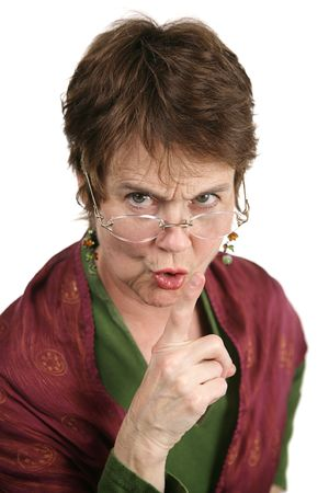 mean: An angry middle aged librarian putting her finger to her lips to tell you to be quiet.  Isolated on white