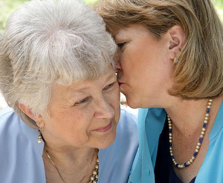 An adult woman kissing her senior mother.  Black and white with vignette. Stock Photo - 806128