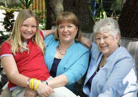 A mother, daughter and grandmother relaxing outdoors.  They are blond, blue eyed and have a strong family resemblance. Stock Photo - 806129