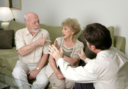 A senior couple in counseling argues as their therapist tries to calm then down.