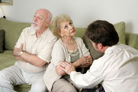 A senior couple in marriage counseling.  They have their backs turned and are ignoring eachother while the therapist tries to reconcile them.  photo