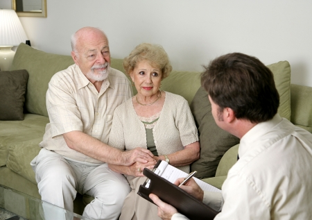 A senior couple talking with a marriage counselor.  Could also be a salesman in their home. photo