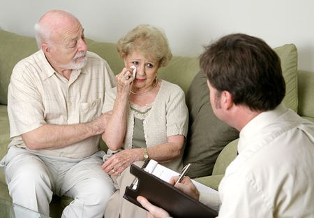 social worker: A senior couple in counseling - either grief counseling or marriage counseling.  The wife is crying and the husband is wiping her tears and trying to console her.