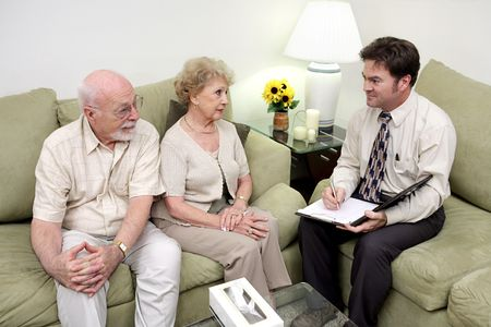 A marriage counselor or salesman meeting with a senior couple.  The wife is receptive but the husband looks skeptical
