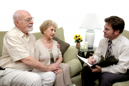 taking a wife: A senior couple speaking with a marriage counselor.  Could also be a salesman in their home.  Isolated on white with focus on couple.