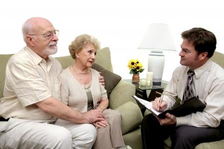 terapia psicologica: Un par mayor que habla con un consejero de la uni�n. Podr�a tambi�n estar un vendedor en su hogar. Aislado en blanco con el foco en pares. Foto de archivo