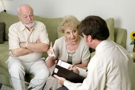 A senior couple in marriage counseling.  Shes complaining to the therapist about her husband while he looks on in disbelief.  Focus on wife.   photo