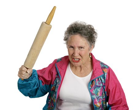 A very angry senior lady holding a rolling pin and threatening to whack someone with it (her husband?).  Isolated on white.