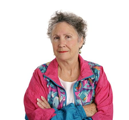 skepticism: A senior woman in a track suit with her arms crossed and a distrustful expression.  Isolated on white. Stock Photo