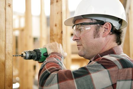 depiction: A construction worker drilling and wearing proper safety equipment according to OSHA regulations.  Authentic and accurate content depiction.