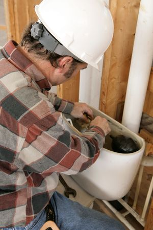 A construction plumber installing a toilet tank in a new building.  Authentic and accurate content depiction.   photo