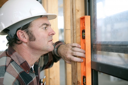 carpenter tools: A horizontal view of a carpenter checking a newly installed window to see if its level.  Authentic and accurate content. Stock Photo