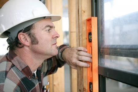 Een horizontale weergave van een timmerman de controle op een nieuw geïnstalleerde venster te zien als het niveau. Authentiek en nauwkeurige inhoud.