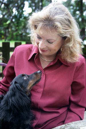 A woman and her long haired daschund looking into eachothers faces with love.  Focus on woman's face. Stock Photo - 834005