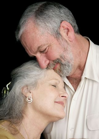 tenderly: A beautiful middle aged couple tenderly embracing eachother.  They are very much in love.  Black background.