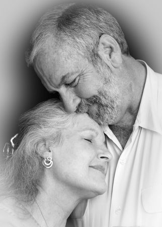 A beautiful middle aged couple tenderly embracing eachother.  They are very much in love.  Black background.