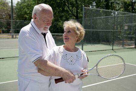一緒にテニスをしている年配のカップル。彼は彼女を示してどのように彼女のラケットのグリップします。