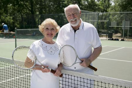 An attractive senior couple ready to play tennis.   photo