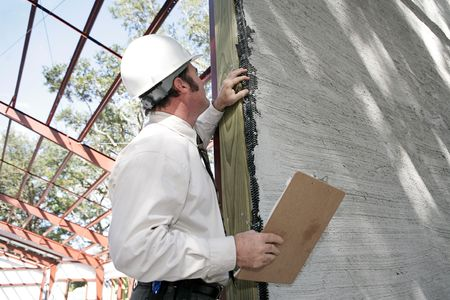 A building inspector checking over incomplete stucco work on new construction. Focus on stucco work.   Banco de Imagens