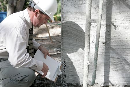 engineering clipboard: A building inspector checking out the foundation of a new building.
