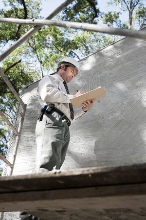 engineering clipboard: A building inspector on scaffolding inspecting the outside second story of a newly constructed building.