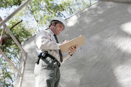 Horizontal view of a construction inspector on scaffolding making notes on his checklist. photo