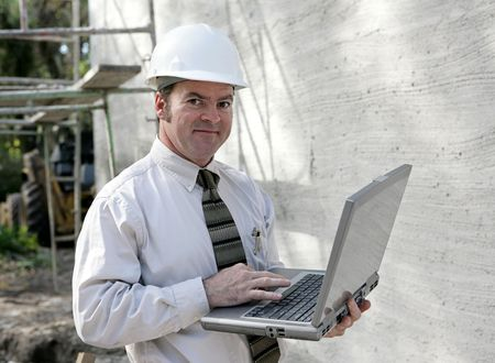 An engineer or building inspector checking building specs on his laptop computer.